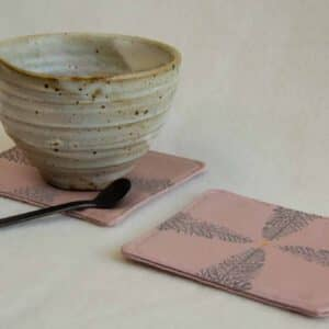 Ceramic tea cup on a pink coaster
