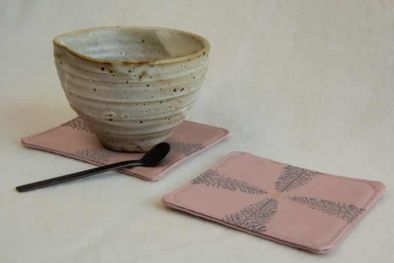 Ceramic tea cup on a pink coaster