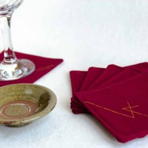 Six burgundy coasters with a wine glass and small dish