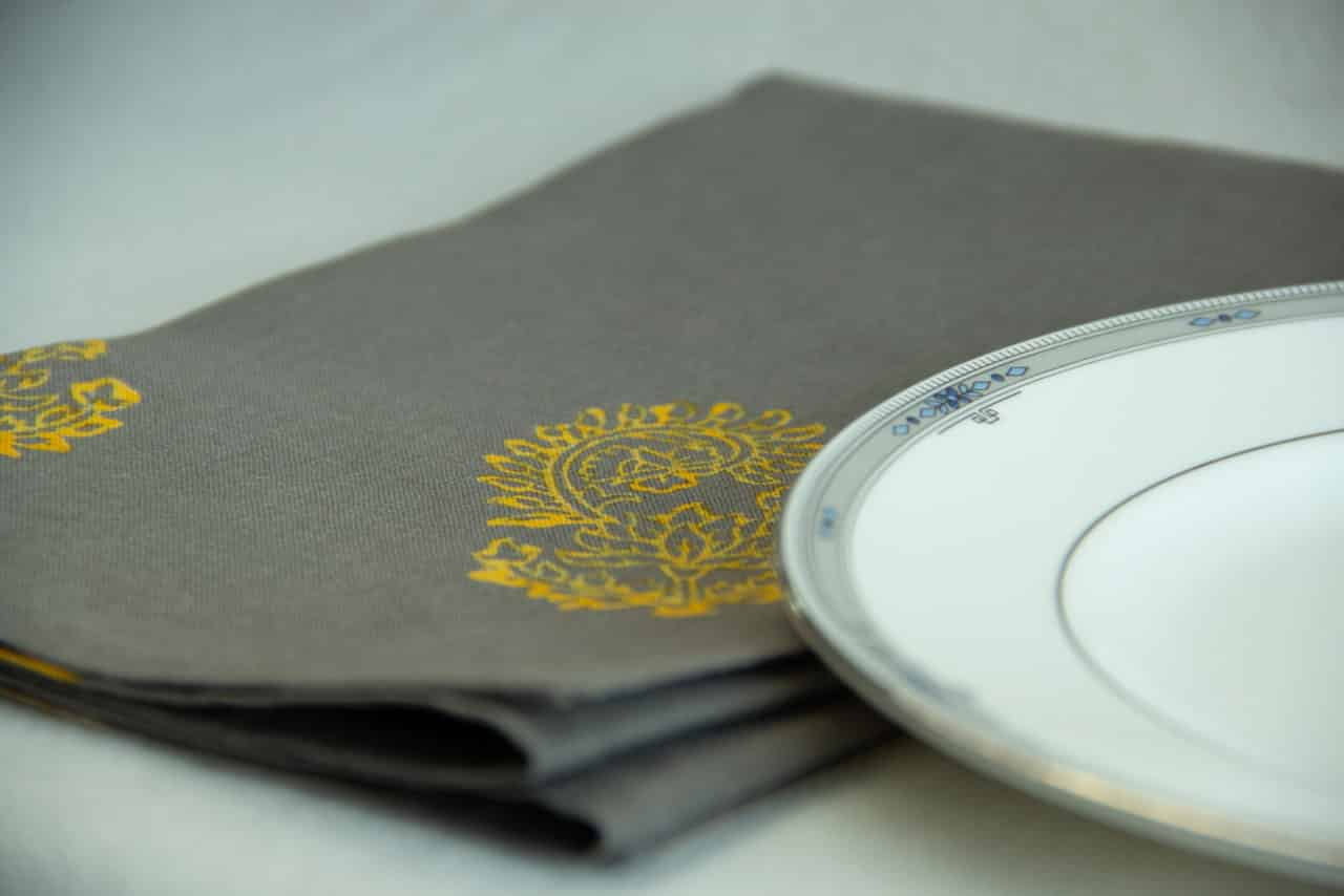 Grey table napkin with yellow floral print, placed next to a white plate