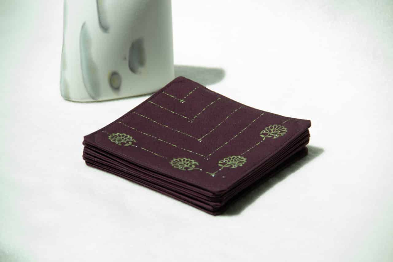Stack of eggplant colored coasters next to a decorative stone.
