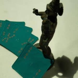 Set of four coasters arranged next to a metal statue