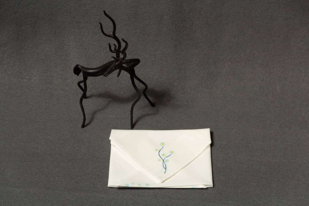 A folded handkerchief with a hand-painted floral design next to a small statue of a horse