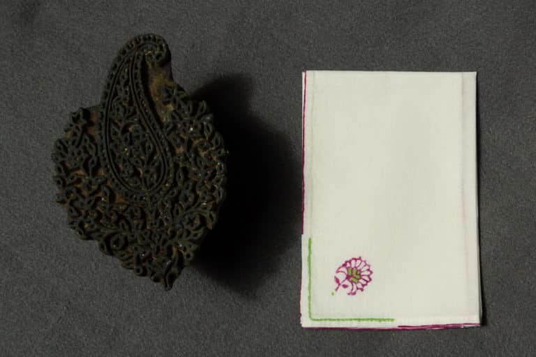 A folded handkerchief with a woodblock printed design next to a woodblock