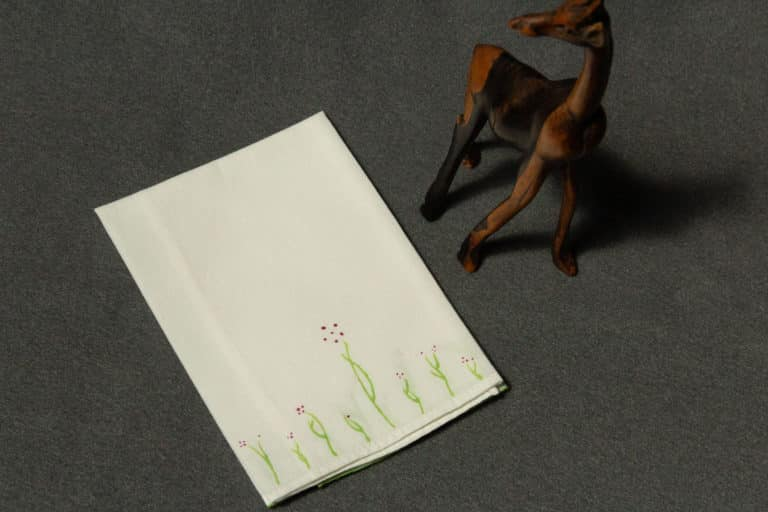 A folded handkerchief painted with small plants with plum colored flowers, next to a small wooden giraffe
