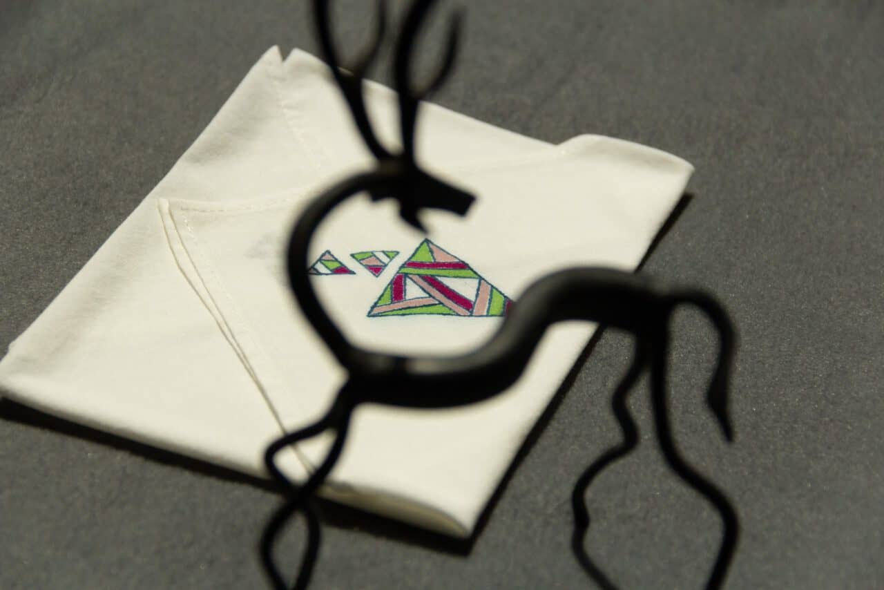 Handkerchief with three colored triangle prints next to a small statue of a horse