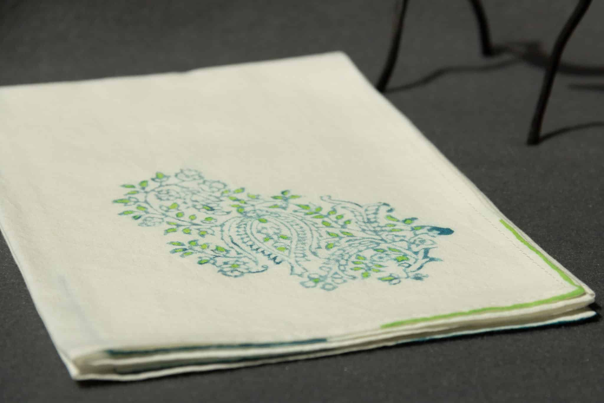A folded handkerchief with a vintage woodblock print in green and blue
