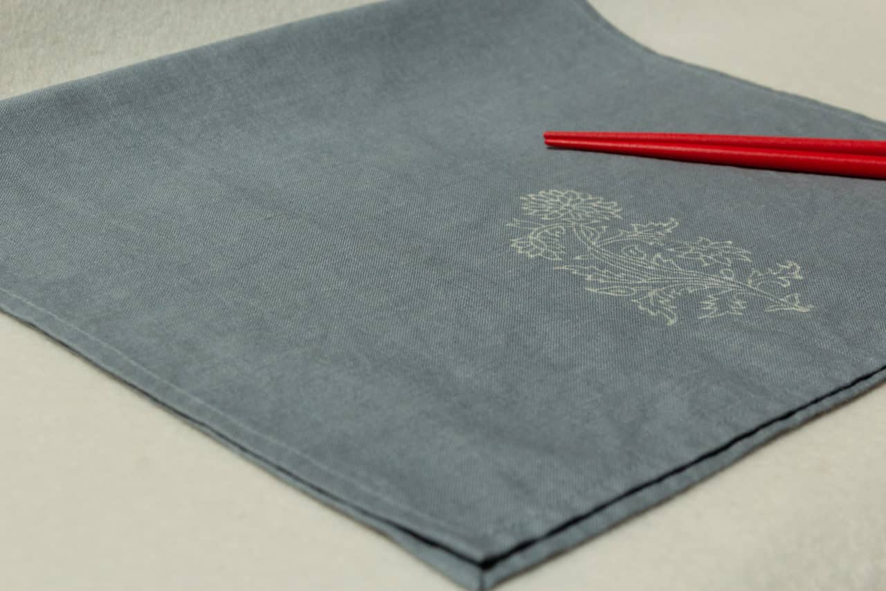 Blue-gray linen hand towel with floral print, and two red chopsticks