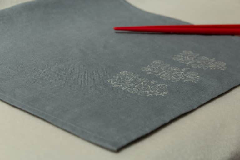 A blue-gray linen napkin with vintage block prints, and two chopstick.