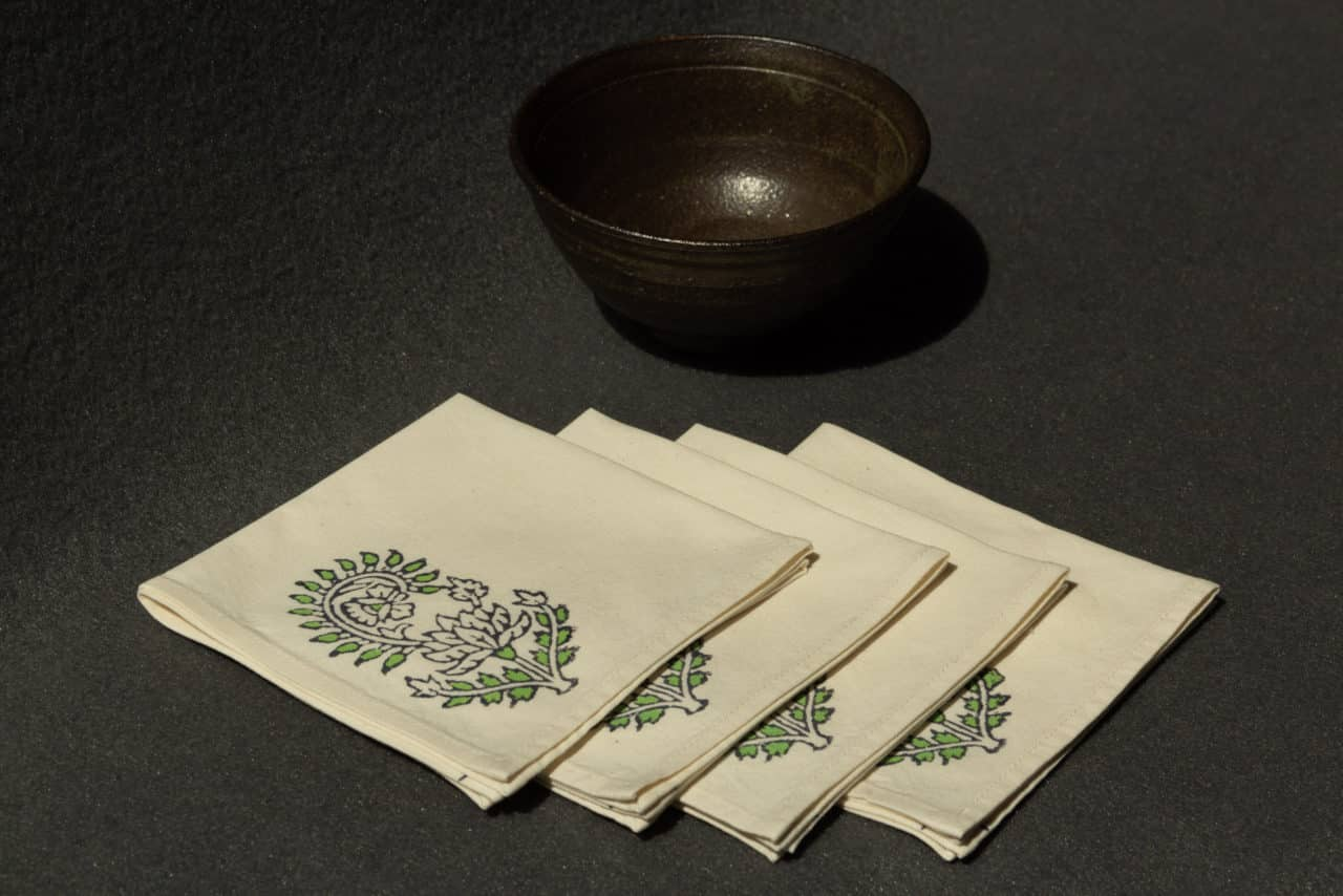 Four napkins with a woodblock print next to a ceramic bowl