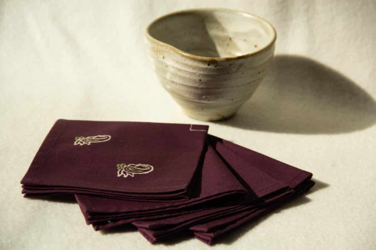 Four deep purple cocktail napkins with cream and green prints next to a ceramic cup.