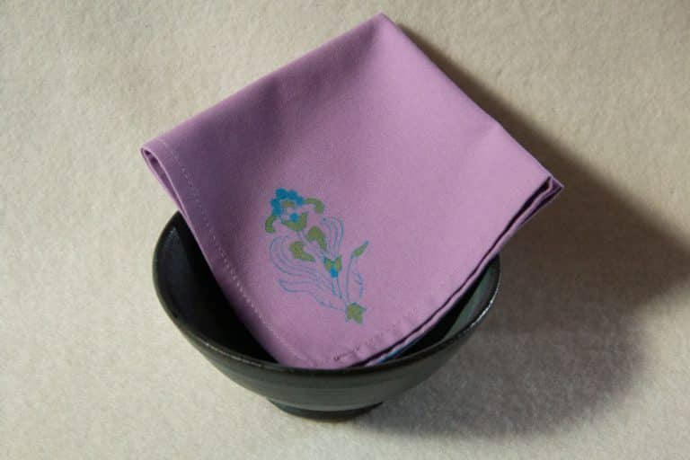 A lilac colored cocktail napkin with a blue and green floral print folded inside a bowl.