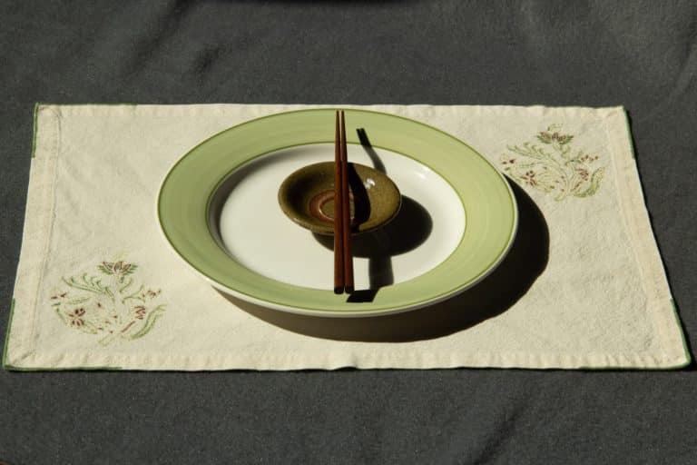 A plate, dipping bowl and chopsticks kept on top of a placemat.