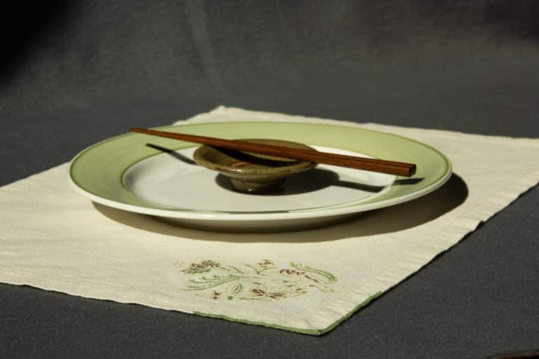Off-white placemat with woodblock printed pattern, shown with a plate, sauce cup and chopsticks on top.