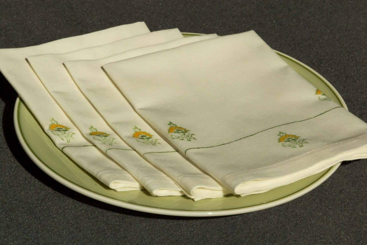 A set of four folded blockprinted napkins on a dinner plate