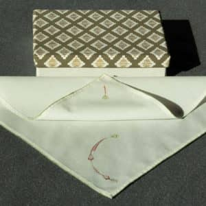 A partially folded handkerchief and an ornamental box