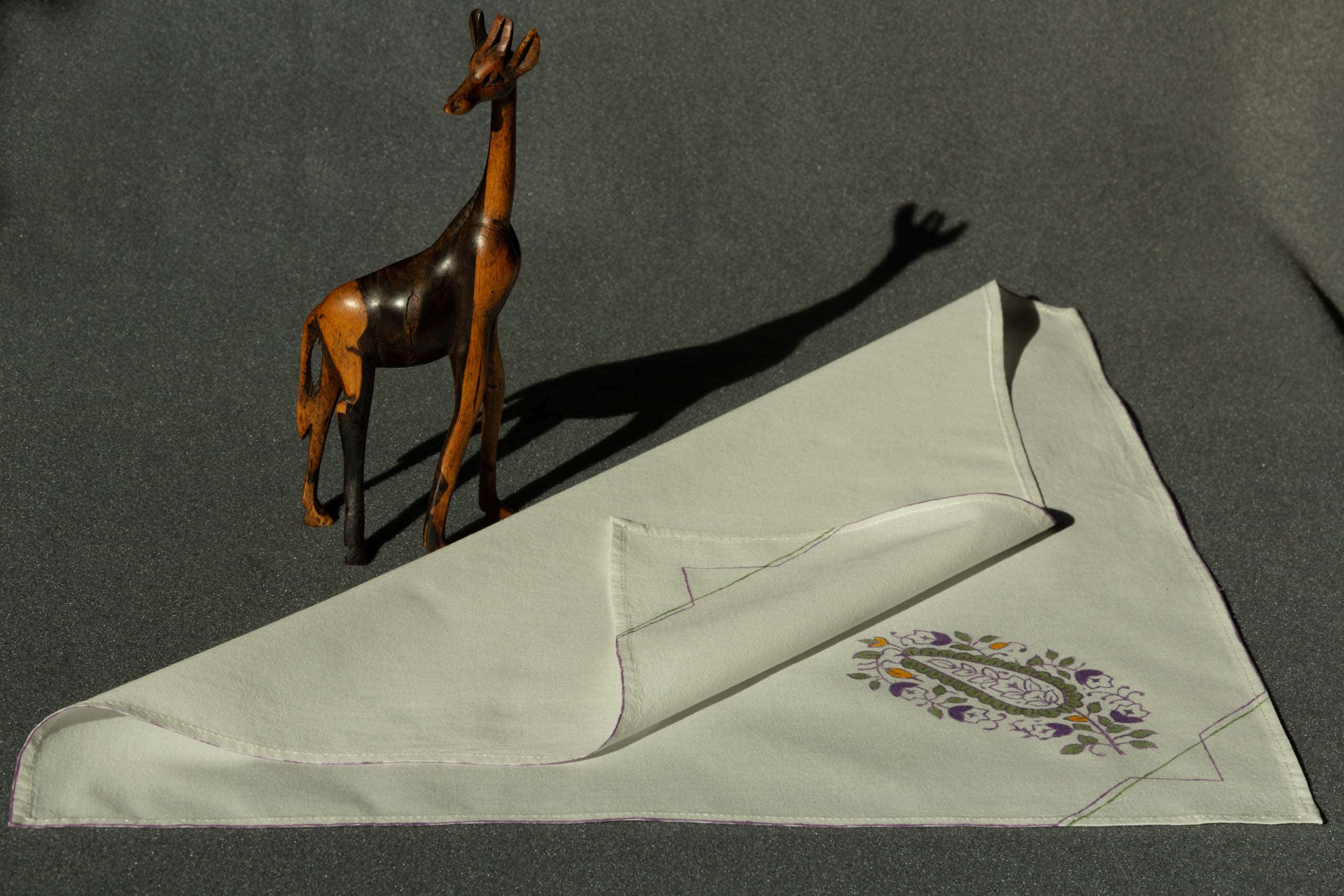 A partially folded handkerchief with a small wooden giraffe next to it