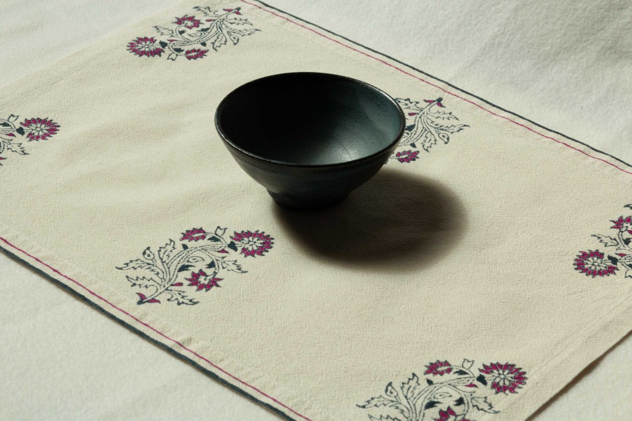 A single placemat with a bowl in the middle