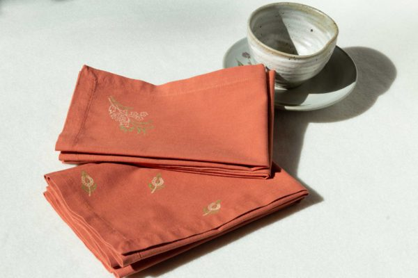 A set of napkins in terracotta with green and cream prints next to a ceramic cup and dish.