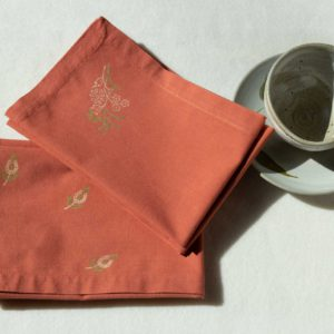 A set of napkins in terracotta color with green and cream prints next to a ceramic cup and plate